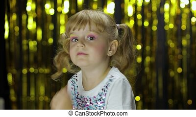 Stylish child dancing fooling around, make faces. Girl posing on background with foil golden curtain