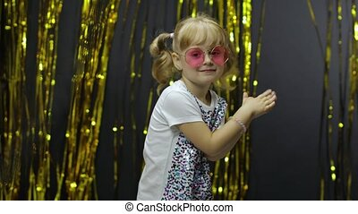Stylish child dancing, make faces, shaking shoulders in silly dance. Little fun blonde kid teen girl 4-5 years old in pink sunglasses fooling around on background with foil fringe golden curtain