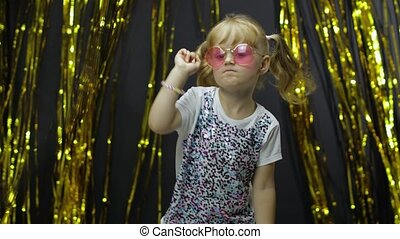 Stylish child dancing, make faces, waving hand in silly dance. Little blonde kid girl 4-5 years old