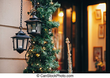 Stylish christmas decorations, garland lights and fir branches with lantern on window of cafe front in european city street. Festive decor and illumination in winter holidays