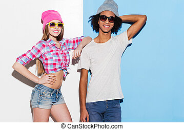 Stylish couple. Funky young couple wearing sunglasses and smiling while standing against colorful background
