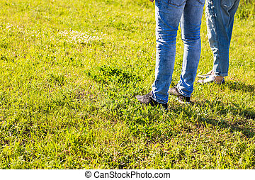 stylish couple legs on sunny grass in meadow in summer, travel together concept, space for text