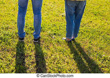 stylish couple legs on sunny grass in meadow in summer, travel together concept, space for text.