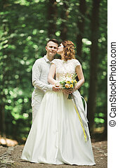 Stylish couple of happy newlyweds walking in the park on their wedding day with bouquet