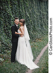 Stylish couple of newlyweds on their wedding day. Happy young bride, elegant groom and wedding bouquet. Portrait of young wedding couple at nature.