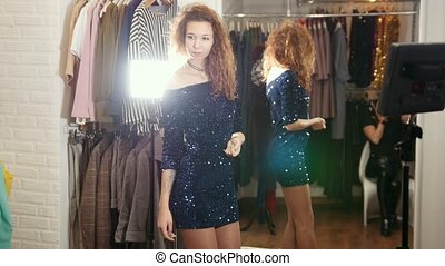 Stylish curly haired woman in evening dress posing for...