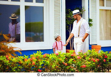 stylish dad and son walking on the caribbean street