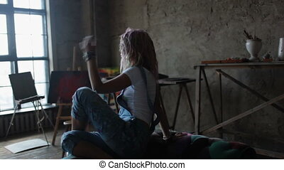 Stylish dancer girl with multicolored hair sitting on the couch