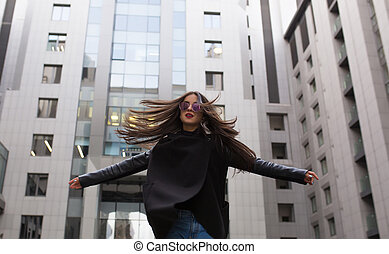 Stylish dressed brunette woman with hair blowing in the wind walking near the city building