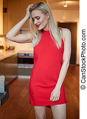 Stylish elegant blonde woman in home living room, wearing red sexy dress