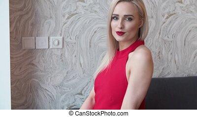 Stylish elegant blonde woman in home living room, wearing...