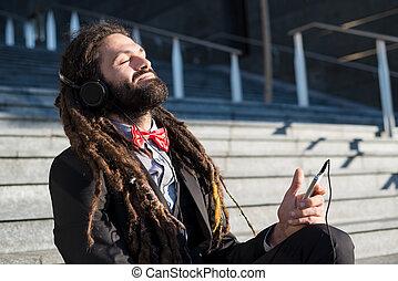 Stylish elegant dreadlocks businessman listening music in...
