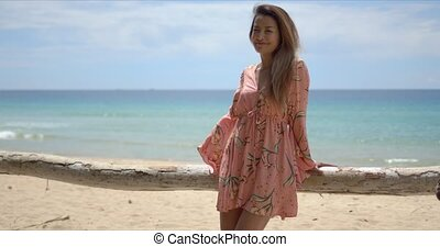 Stylish ethnic woman leaning on fence on beach - Relaxed ...