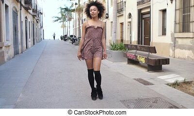 Stylish ethnic woman strolling on street - Young beautiful...