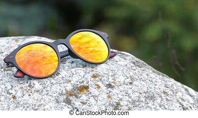 Red, positive, Stylish sport eyeglasses on rock