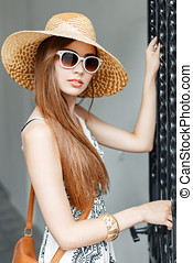 Stylish fashionable girl in sunglasses and a hat on a summer sunny day.