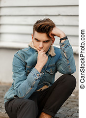 Stylish fashionable portrait of a young guy with a haircut in a fashion jeans jacket near a wooden wall