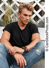 Stylish fashionable young model man in black T-shirt with jeans sitting on the beach