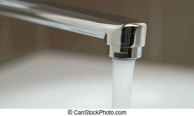 Flow of water pouring from chrome-plated faucet
