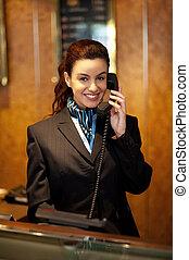 Stylish female attendant at hotel reception communicating on...