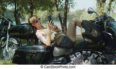Stylish female biker relaxing with phone on bike - Slim...