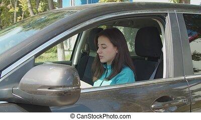 Stylish female driver applying lipstick in car