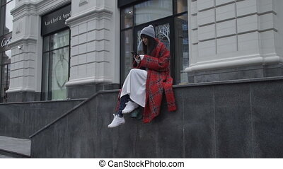 Stylish female sitting on city street stairs