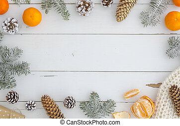 stylish festive New year, Xmas, merry christmas frame from decorations, fir cones and branch, knitted scarf, gift, orange mandarin on white wooden planks table Top view. Trendy cozy design background .