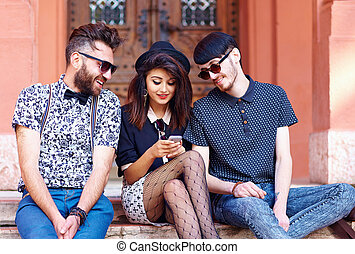 stylish friends having fun together with the phone