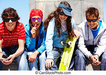 Row of several teens in sunglasses looking at camera
