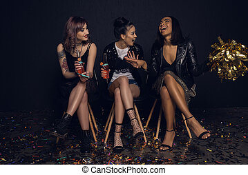 stylish friends sitting on chairs and enjoying party together