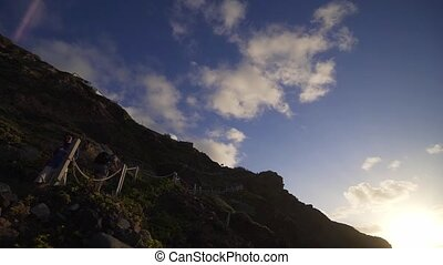 Stylish girl goes down the cliff at sunset. Steep stairs off the coast of the Atlantic Ocean, descent to the wild beach of Benijo. Accessibility and amenities for tourists fullhd