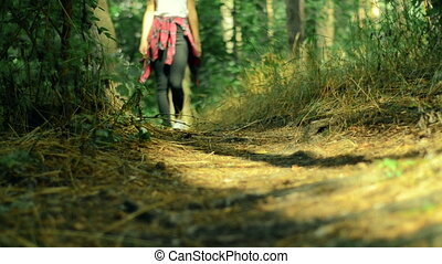 stylish girl goes on a footpath in the forest