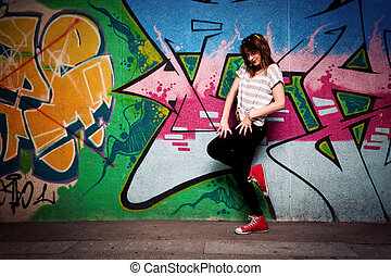 Stylish fashionable girl in a dance pose against colorful graffiti wall. Fashion, trends, subculture. Full body shot