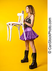 Stylish girl in boots and a skirt is standing and holding a chair