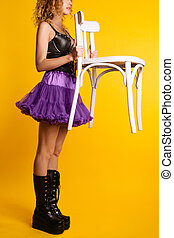 Stylish girl in boots and a skirt is standing and holding a white chair