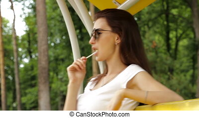 stylish girl in glasses licks a lollipop and sits on a swing