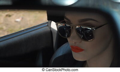 stylish girl in glasses looks in the mirror of the car