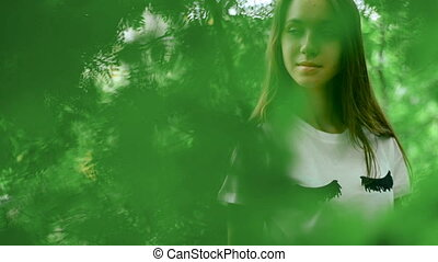 stylish girl in green forest poses behind the leaves -...