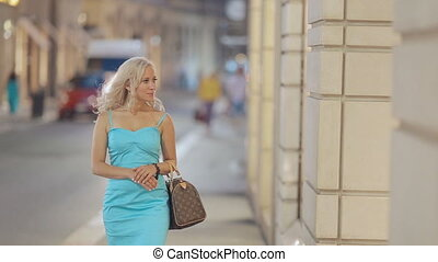 Stylish girl looking in the shopwindow of luxury clothing stores