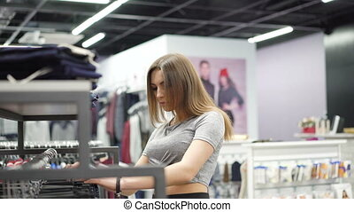 Stylish girl looking on clothes in fashionable boutique. 4K