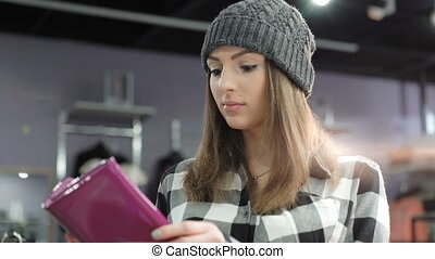 Stylish girl looking on purse in fashionable boutique.