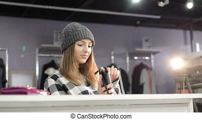 Stylish girl looking on purse in fashionable boutique. 4K -...