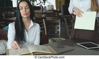 Stylish girl looks at food menu of the restaurant and orders food from the waiter