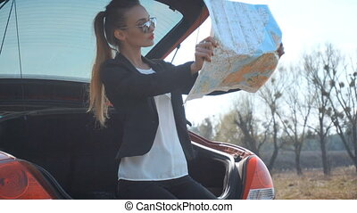 girl sits in the trunk and sees a map of the area