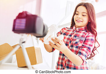 Stylish and beautiful curly girl standing in front of her camera while filming blog