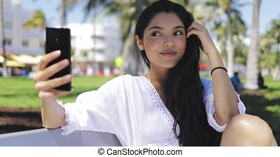 Stylish girl taking selfie on bench in park