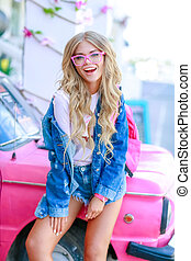 Stylish girl with denim jacket near the pink car with a pink bag.