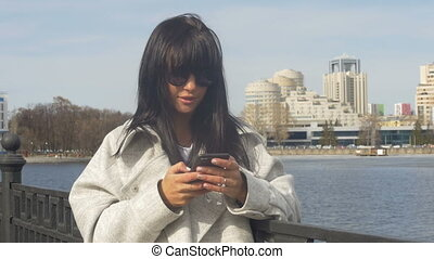 Stylish girl with phone on seafront