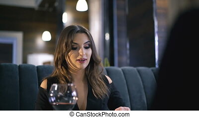 Stylish girls eating, drinking wine and speaking at fashionable restaurant 4K